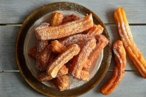 Churros,Sprinkled,With,Powdered,Sugar,On,A,Plate,On,A